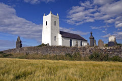 Chiesa di Ballintoy dell'Irlanda sopra il campo dell'orzo, Antrim Immagine Stock