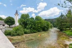Chiesa di Bohinj, Slovenia - vista del fiume nel villaggio di Ribcev Laz Turista sul kajak e sulla canoa sul fiume Facendo un'esc fotografie stock