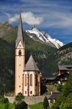 Chiesa di Heiligenblut davanti al picco di Grossglockner Fotografia Stock