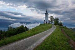 Chiesa di Jamnik su un pendio di collina in primavera, tempo nebbioso al tramonto in Slovenia, Europa Paesaggio della montagna po Immagine Stock