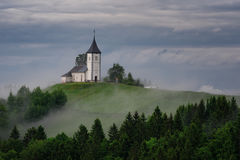Chiesa di Jamnik su un pendio di collina in primavera, tempo nebbioso al tramonto in Slovenia, Europa Paesaggio della montagna po Fotografie Stock