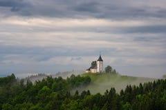 Chiesa di Jamnik su un pendio di collina in primavera, tempo nebbioso al tramonto in Slovenia, Europa Paesaggio della montagna po Immagini Stock Libere da Diritti