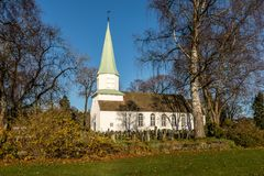 Chiesa di legno bianca veduta dal lato, dagli alberi, dall'erba e dal cielo blu in autunno, Kristiansand, Norvegia Fotografie Stock Libere da Diritti