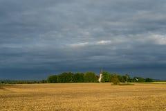 Chiesa di Marys, campo di grano, cielo blu ed ambiente naturale Torma di estate, piccolo villaggio in Estonia europa Fotografia Stock