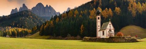 Chiesa di San Giovanni in Ranui al tramonto con il gruppo dolomitico di Odle su fondo Val di Funes, Italia Fotografia Stock