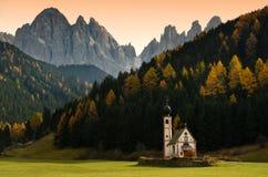 Chiesa di San Giovanni in Ranui al tramonto con il gruppo dolomitico di Odle su fondo Val di Funes, Italia Fotografia Stock Libera da Diritti