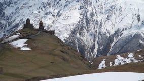Chiesa di trinità di Gergeti contro il contesto delle montagne innevate: archivi video