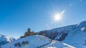 Chiesa di trinità di Gergeti ed il sole di pomeriggio, Kazbegi, Georgia Immagine Stock Libera da Diritti