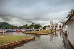 Chiesa e vecchie case con il marciapiede di pietra sommerso in Paraty Fotografia Stock