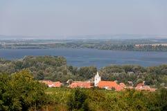 Chiesa e villaggio vicino al lago, cielo blu Immagini Stock Libere da Diritti