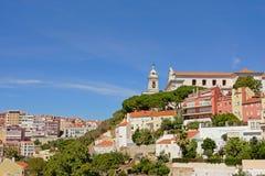 Chiesa ed alberi su una collina sopra le case di Lisbona Immagine Stock