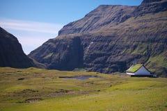 Chiesa tradizionale circondata dalle alte montagne in villaggio Saksun sull'isola Streymoy delle isole faroe fotografia stock libera da diritti