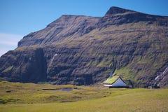 Chiesa tradizionale circondata dalle alte montagne in villaggio Saksun sull'isola Streymoy delle isole faroe fotografia stock