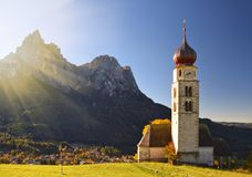 Chiesa tradizionale del Tirolo nelle colline pedemontana delle dolomia sotto il sole di autunno Immagine Stock Libera da Diritti