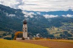 Chiesa tradizionale del Tirolo nelle colline pedemontana delle dolomia sul fondo rurale della montagna Fotografia Stock