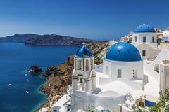 Chiese a cupola blu nel villaggio di OIA, Santorini Thira, isole di Cicladi, mar Egeo, immagine stock libera da diritti