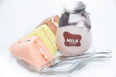 Chiffongkakor med en flaska av mjölkar på plattan Arkivbild