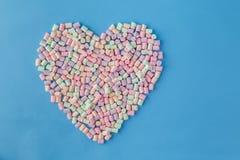 Chiffre de forme de coeur de guimauve colorée sur le fond bleu Photos stock