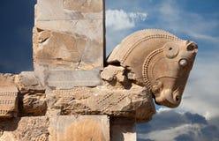 Chiffre de Taureau de dynastie d'Achaemenid comme capital de colonne dans Persepolis de l'Iran contre le ciel bleu nuageux Photos stock