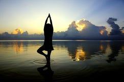 Chiffre de yoga de Madame avec la scène de coucher du soleil Images libres de droits
