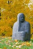 Chiffre en pierre religieux d'une femme contre les arbres automnaux Photographie stock libre de droits