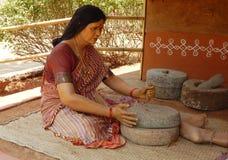 Chiffre indien rural de femme utilisant la broyeur en pierre pour faire la farine Photo libre de droits