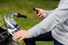 Chiffre masculin sur le vélo avec le smartphone photographie stock libre de droits