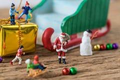 Chiffre miniature le père noël avec le fonctionnement et le sta heureux d'enfants Photographie stock
