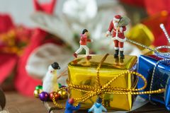 Chiffre miniature le père noël se tenant sur le grand cadeau actuel d'or Photos stock