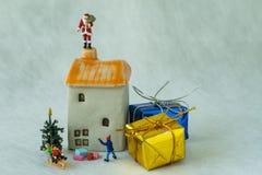 Chiffre miniature le père noël se tenant sur la cheminée et le childr de toit images stock