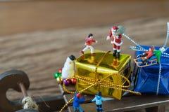 Chiffre miniature le père noël se tenant sur la grande boîte actuelle sur le slei Photographie stock libre de droits