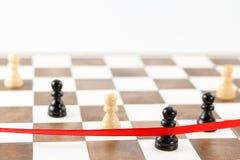 Chiffre noir du ` s de gage croisant le ruban de finition Direction d'échecs Photo stock
