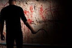 Chiffre ombragé près de mur souillé par sang image stock
