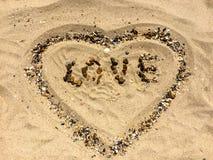 Chiffres d'AMOUR et de COEUR sur un sable Photographie stock libre de droits