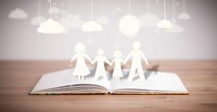 Chiffres de carton de la famille sur le livre ouvert Images stock
