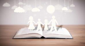 Chiffres de carton de la famille sur le livre ouvert Photos stock