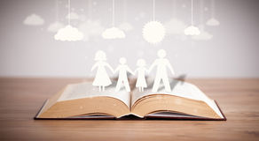 Chiffres de carton de la famille sur le livre ouvert Images libres de droits