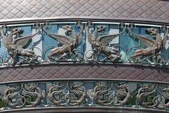 Chiffres de cuivre des dragons et des lions à ailes sur le bâtiment Images libres de droits