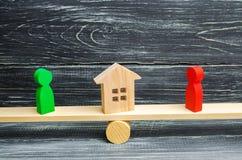 Chiffres en bois sur les échelles clarification de la propriété de la maison, immobiliers cour rivaux dans les affaires concurren Images libres de droits