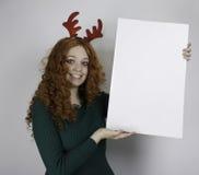 Chifres vestindo da jovem mulher e guardar o sinal vazio Fotografia de Stock
