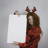 Chifres vestindo da jovem mulher e guardar o sinal vazio Imagens de Stock Royalty Free