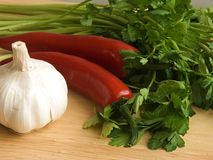 ChiIli, garlic & parsley II. Chilli and garlic on a wooden chopping board Royalty Free Stock Photos