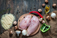 Chiken breast On a cutting board with herbs different fruits and vegetables on rustic wooden background top view Stock Photography