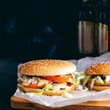 Chiken hamburgare och flaskor av öl arkivfoto