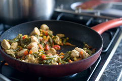 Chiken meat and vegetables cooking in red frying pan. On black kitchen stove at home Stock Photo