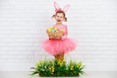 Chil feliz en el conejito de pascua del traje con los huevos y el ingenio de la hierba verde Fotografía de archivo