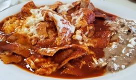 Chilaquiles, мексиканская еда с фасолями, сыром и горячим томатным соусом над tortilla стоковая фотография rf