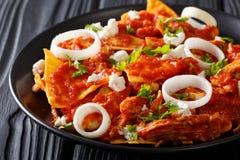 Chilaquiles mexicanos calientes de la comida con el primer del pollo en una placa H Imagenes de archivo