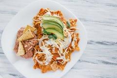 Chilaquiles rojos med mexikansk mat Mexiko för höna och för avokadot frukosterar arkivfoton