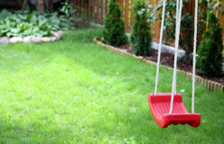 Child's swing on green grass Royalty Free Stock Image